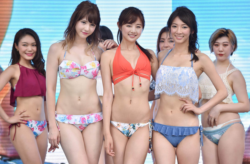 Models wearing new bikinis pose for the media following a promotional flash mob dance performance in Tokyo on July 17, 2017. The event was organized by the Japan Swimsuit Association to promote the latest swimsuits. / AFP PHOTO / KAZUHIRO NOGI