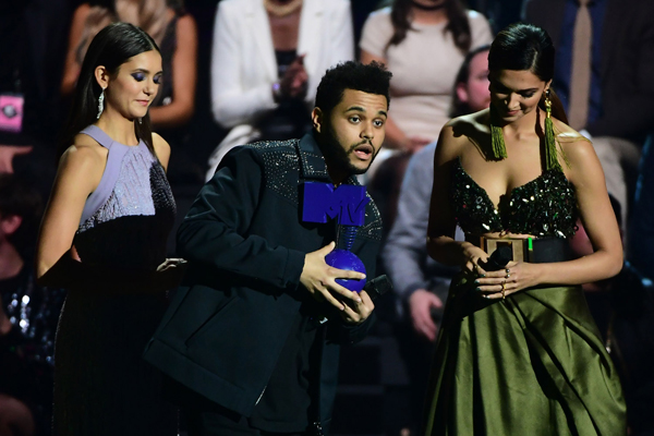 Canadian singer The Weeknd (C) receives the Best Video Award from Bulgarian-Canadian actress Nina Dobrev (L) and Indian film actress Deepika Padukone at the MTV Europe Music Awards (EMA) on November 6, 2016 at the Ahoy Rotterdam in Rotterdam. / AFP PHOTO / Emmanuel DUNAND