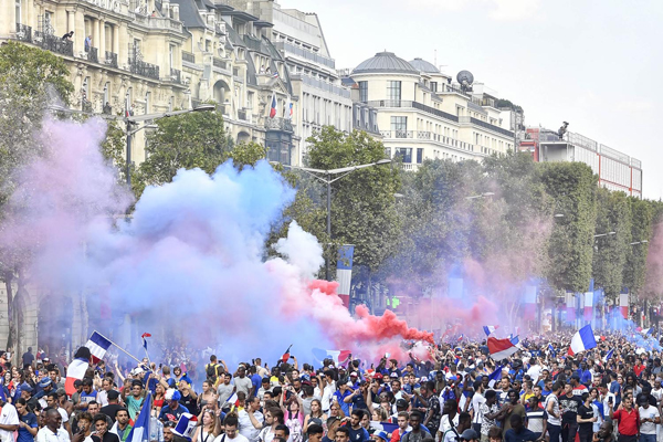 (180716) -- PARIS, July 16, 2018 (Xinhua) -- Fans celebrate on the Champs-Elysees Avenue for the championship of the French team in Paris, France on July 15, 2018. The French soccer team beat the Croatia team by 4-2 and claimed the title in the final of the 2018 FIFA Russian World Cup. (Xinhua/Chen Yichen)