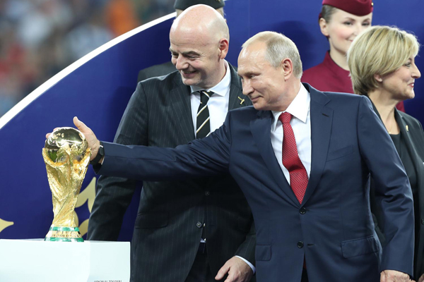 (180715) -- MOSCOW, July 15, 2018 (Xinhua) -- Russian President Vladimir Putin (R front) touches the World Cup trophy at the awarding ceremony after the 2018 FIFA World Cup final match between France and Croatia in Moscow, Russia, July 15, 2018. France defeated Croatia 4-2 and claimed the title. (Xinhua/Fei Maohua)