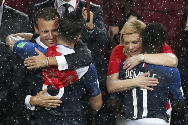 French President Emmanuel Macron, left, and Croatian President Kolinda Grabar-Kitarovic congratulate French players on their victory as they are presented with medals after the final match between France and Croatia at the 2018 soccer World Cup in the Luzhniki Stadium in Moscow, Russia, Sunday, July 15, 2018. France won the final 4-2. (AP Photo/Rebecca Blackwell)