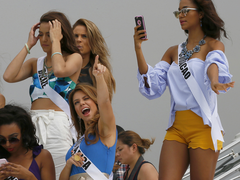 Miss Universe contestant Carolina Duran of Costa Rica, center, reacts to a TV network's drone as others prepare to pose from the deck of the yacht Happy Life prior to cruising to a beach resort in Batangas province Thursday, Jan. 19, 2017 at the Philippine Navy headquarters in Manila, Philippines. Eighty-six candidates from around the world are vying for the title to succeed Pia Wurtzbach from the Philippines. The competition takes place on Jan. 30. They are, from left, Cherell Williamson of Bahamas, Rebecca Rath of Belize, Hildur Maria of Iceland, and Chanelle de Lau of Curacao. (AP Photo/Bullit Marquez)