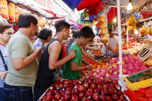 People buy round fruits as part of the preparations to welcome the New Year, Saturday, Dec. 31, 2016 in Manila, Philippines. Filipinos usually put at least twelve different round fruits that have the circular shape of coin money on their dinning table to symbolize prosperity for the coming New Year. (AP Photo/Bullit Marquez)