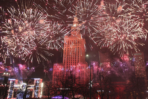 Spectators watch fireworks in front of the Palace Kultury during the New Year celebrations in Warsaw, Poland, Sunday, Jan. 1, 2017. Thousands of Warsaw residents took to the streets in the capital to usher in the New Year. (AP Photo/Czarek Sokolowski)