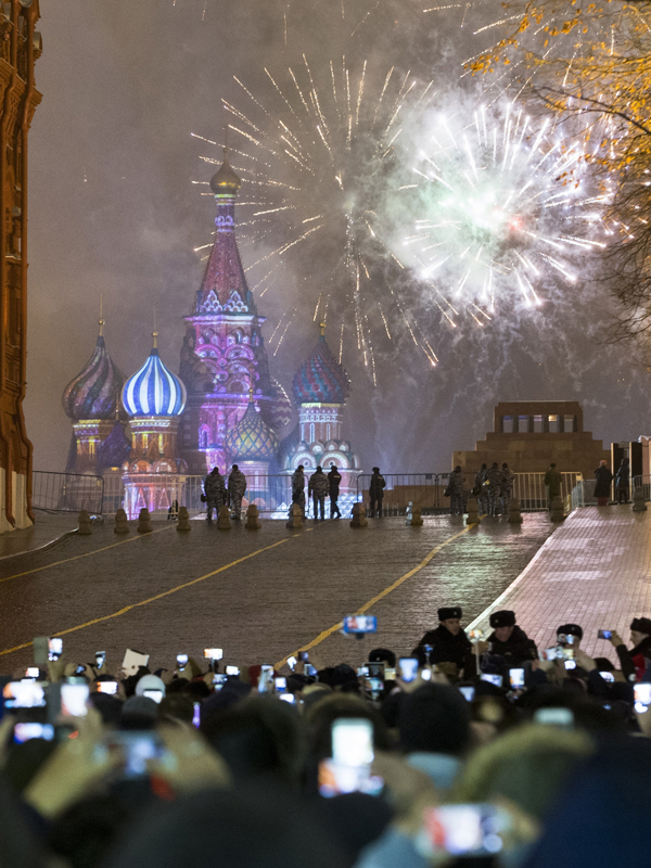 People watch and take pictures with their cell phones as fireworks explode over the Kremlin at Red Square which was blocked by police during New Year celebrations in Moscow, Russia, Sunday, Jan. 1, 2017. New Year's Eve is Russia's major gift-giving holiday, and big Russian cities were awash in festive lights and decorations. (AP Photo/Alexander Zemlianichenko Jr)