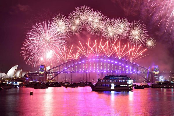 Fireworks erupt over Sydney's iconic Harbour Bridge and Opera House during the New Years Eve fireworks show on January 1, 2017. / AFP PHOTO / PETER PARKS