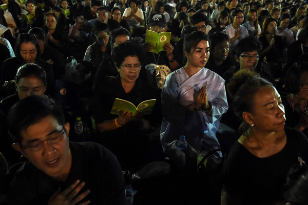 People pray for the late Thai King Bhumibol Adulyadej during New Years celebrations in front of the Grand Palace in Bangkok on December 31, 2016. / AFP PHOTO / LILLIAN SUWANRUMPHA