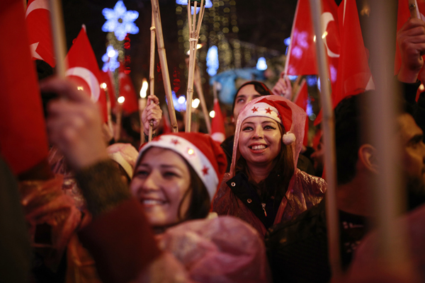 People, some holding Turkish flags and some wearing Santa Claus hats participate during New Year's cerebrations in Istanbul's Ortakoy district by the Bosphorus, during New Year's cerebrations, late Saturday, Dec. 31, 2016. (AP Photo/Emrah Gurel)