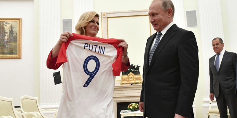 Croatian President Kolinda Grabar Kitarovic, left, presents a T-shirt to Russian President Vladimir Putin as Russian Foreign Minister Sergey Lavrov, right, looks at them during the meeting in the Kremlin in Moscow, Russia, Sunday, July 15, 2018. (Yuri Kadobnov/Pool Photo via AP)